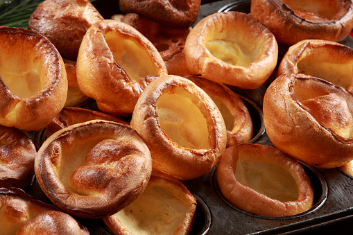 Yorkshire Pudding on Baking Tray with wood and decorative festive background